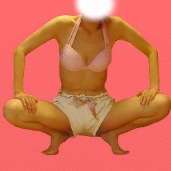 ショートパンツとピンクのビキニで股を開いて膝に両手を置いて座っている