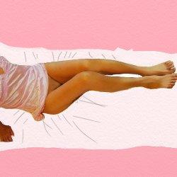 ピンクのベビードールで下半身裸で脚を見せて座っている