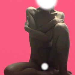 裸で片足を立てて座り、両手で胸を抱えている