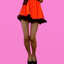 オレンジ色のヒラヒラした三ニスカで脚をそろえて膝を少し曲げて立っている