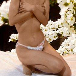 バックは白い花で下着姿で胸を抑えて座っている