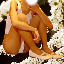白い花をバックに白いレオタードで少しだけ股を開いて体育座りしている